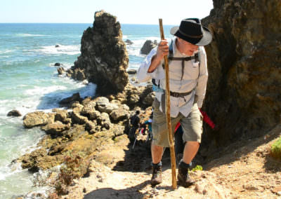 Hikers head away from beach toward lookout point.